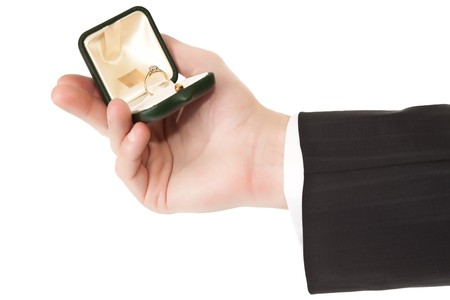 Man in suit holding engagement ring on white isolated background photo