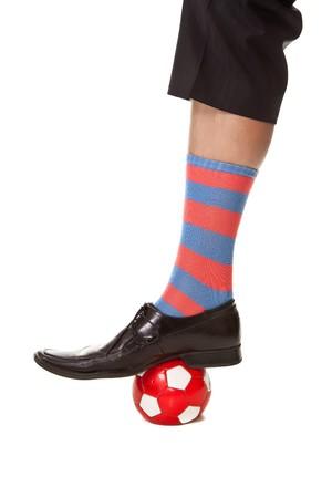 Businessman leg in colorfull socks and soccer ball photo