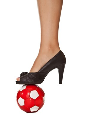 Caucasian blond business woman leg in high heel with soccer ball photo