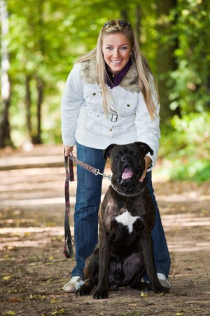 Caucasian young adult blond woman outdoor with boxer dog fall time photo