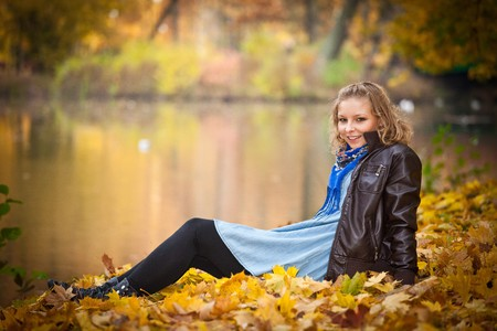 Young caucasian student girl in golden autumn park photo