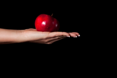 temptations: Woman holding red apple on black background Stock Photo
