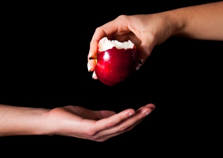 eden: Woman hand giving an apple to man on black background Stock Photo