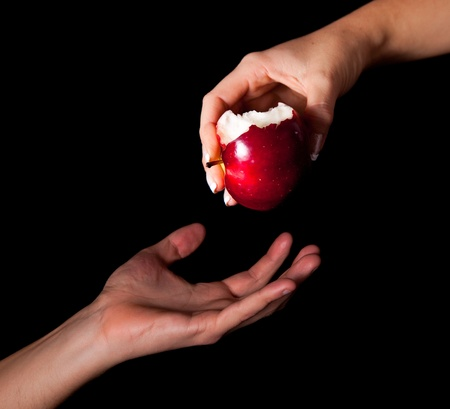 woman apple: Woman hand giving an apple to man on black background Stock Photo