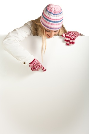 Woman in colorful hat and gloves peeping from behind whiteboard isolated on white Stock Photo - 8353204