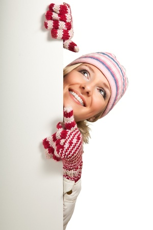 Woman in colorful hat and gloves peeping from behind whiteboard isolated on white photo