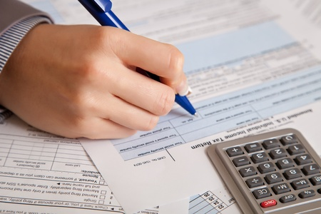 taxpayer: Woman hand filling income tax forms with calculator