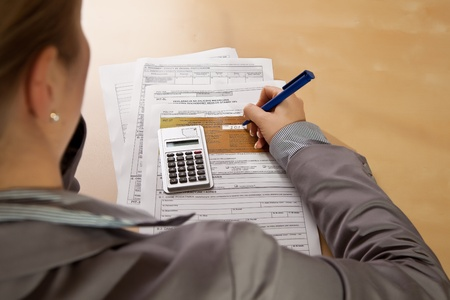 Woman hand filling income tax forms with calculator photo