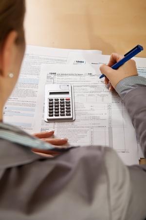 podatnika: Ręce kobiety, wypełnianie formularzy podatku dochodowego z Kalkulatora