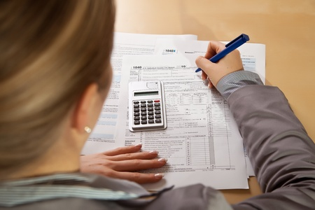 federal tax return: Woman hand filling income tax forms with calculator