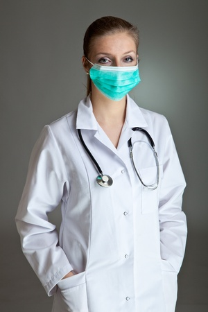 Medical doctor woman in uniform with stethoscope on neutral gray photo