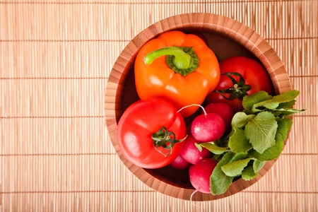 Different ripe vegetables compositions in studio laying on bamboo plate photo