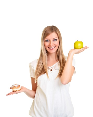 Woman choosing apple over puff cookie isolated on white photo