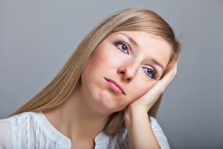 Depressed, sad woman on neutral background photo