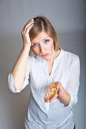 Woman holding pharmaceuticals on neutral bg Stock Photo - 9122557