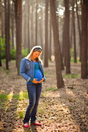 Pregnant woman sitting on green field photo