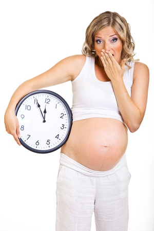 Pregnant woman with clock isolated on white Stock Photo - 9657378