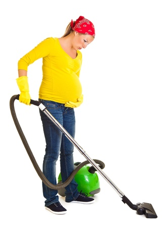 Pregnant woman clean with vacuum cleaner isolated on white photo