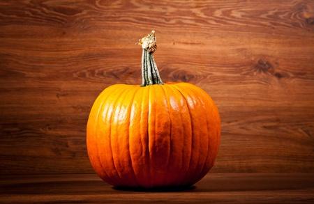 Ripe pumpkin fruits on wooden background photo