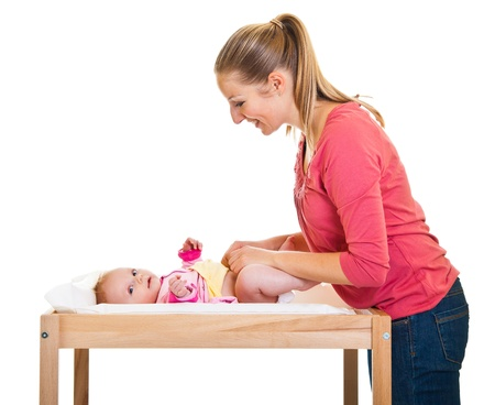 Mother changing little girls diaper on nursery table  Stok Fotoğraf