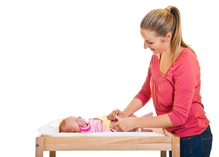 diaper changing table: Mother changing little girls diaper on nursery table  Stock Photo