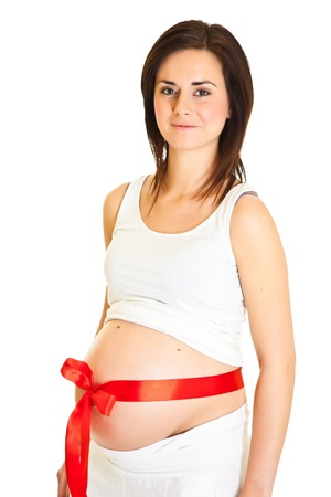 Brunette pregnant woman with red ribbon isolated on white photo