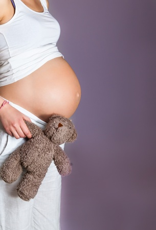 lovely pregnant woman: Pregnant woman on violet background Stock Photo