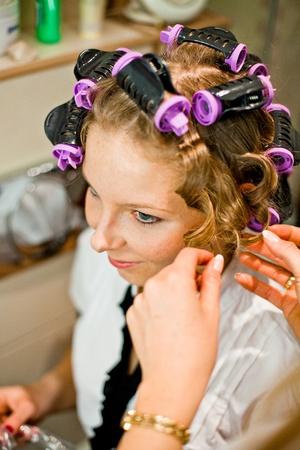 Woman curling hair 写真素材