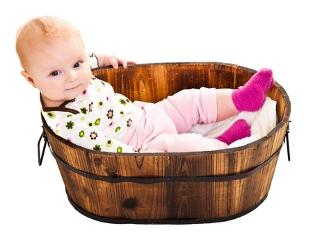 Cute infant girl sitting in wooden bucket photo
