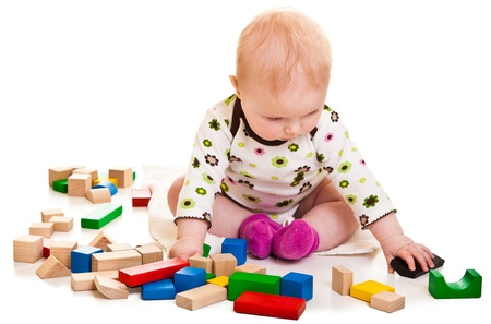 Infant girl playing with building bricks isolated on white photo