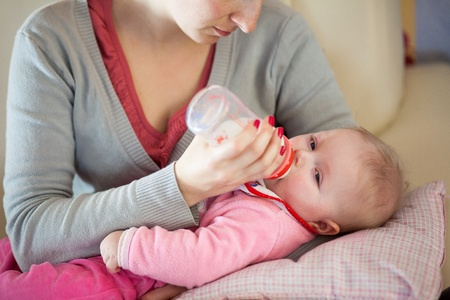 Mother feeding infant girl with a milk bottle photo