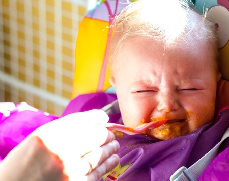 Unhappy infant girl learning to eat solid food 写真素材