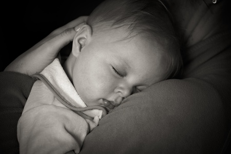 Sleeping infant in mothers arms photo