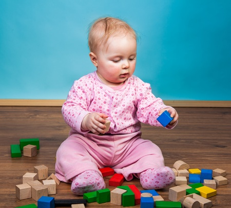 Infant girl playing in room on wooden floor photo