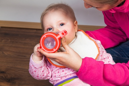 Mother feeding infant girl with a tea bottle photo