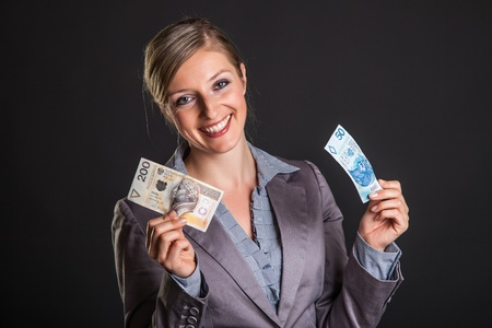 Woman with polish zloty money on dark gray background Stock Photo - 12946645