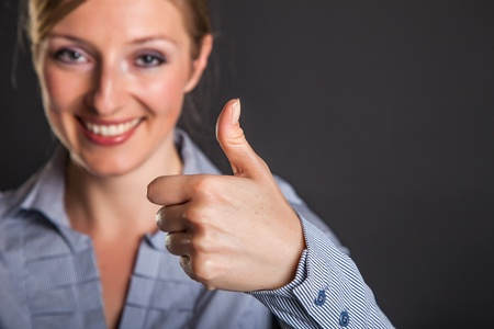 Businesswoman thumbs up on gray background photo