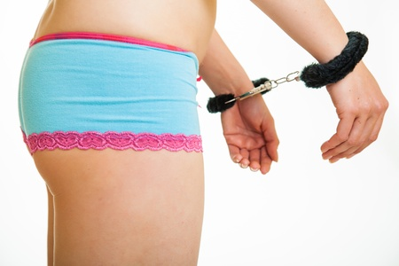Girl in panties and handcuffs isolated on white photo