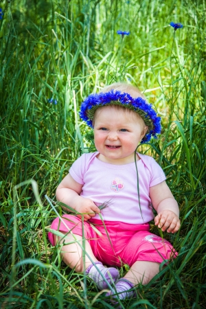 Cute infant baby girl sitting in grass Stock Photo - 13964600