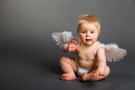 Infant baby with angel wings on neutral background photo