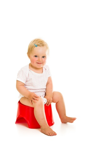 Toddler girl potty trainting isolated on white photo