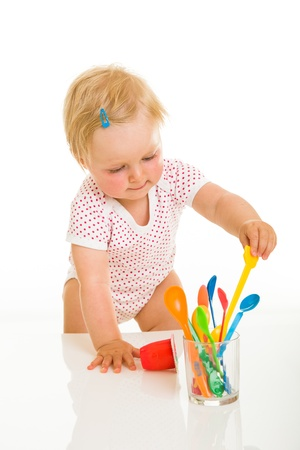 Cute infant girl learining to eat with spoon photo