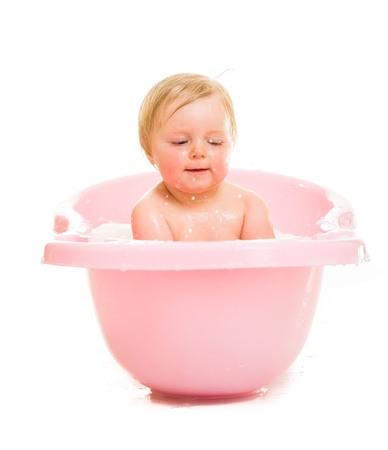 Cute infant girl in bath isolated on white photo