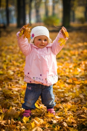 Infant baby girl in golden autumn park Stok Fotoğraf