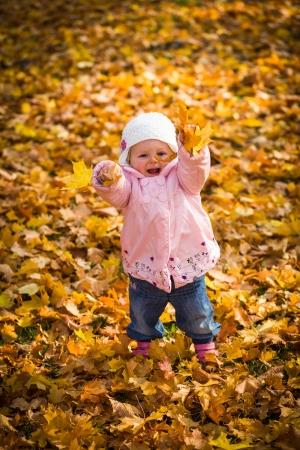 Infant baby girl in golden autumn park photo