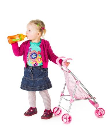 Baby girl drinking tea from bottle photo