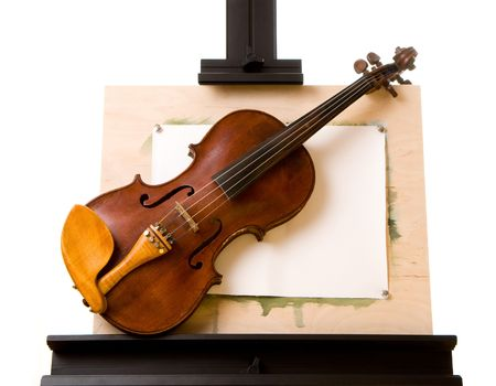 Old violin laying on painting easel isolated on white photo