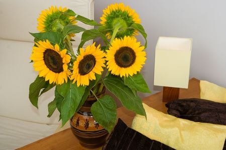 Blooming sunflowers by the bed in a cozy room photo