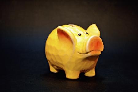 Yellow ceramic piggy coin bank, money savings concept  Stock Photo