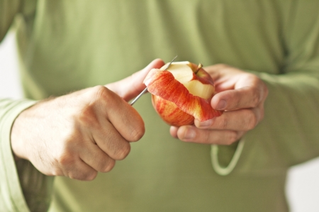 Man hands peeling an apple, close up of hands